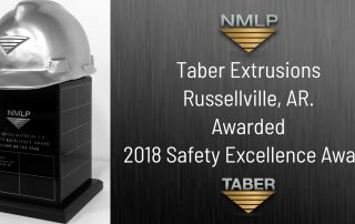 "NMLP Safety Award image of a large black rectangular trophy with a silver hardhat on top donning the ""NMLP inverted triangle"" logo with the words ""Taber Extrusions Awarded 2018 Safety Excellence Award."""