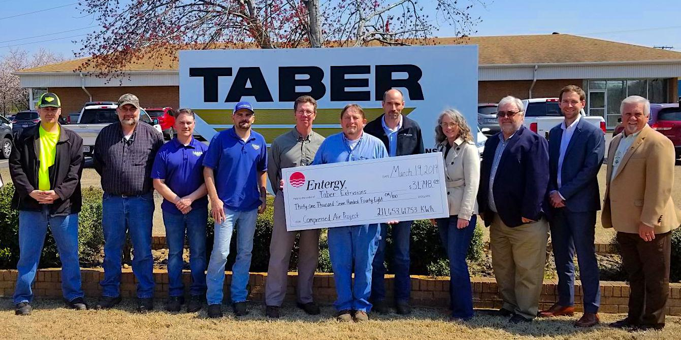 Taber Extrusions staff alongside members from Entergy Incentive Program, CLEAResult, and Arkansas Industrial Machinery, being presented a large rebate check for energy savings.