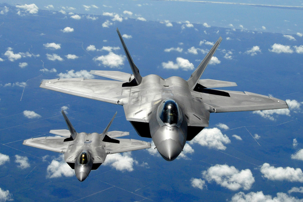 Dramatic in-flight photo of two F-22 Raptor military aircraft speed through the sky on a clear day.