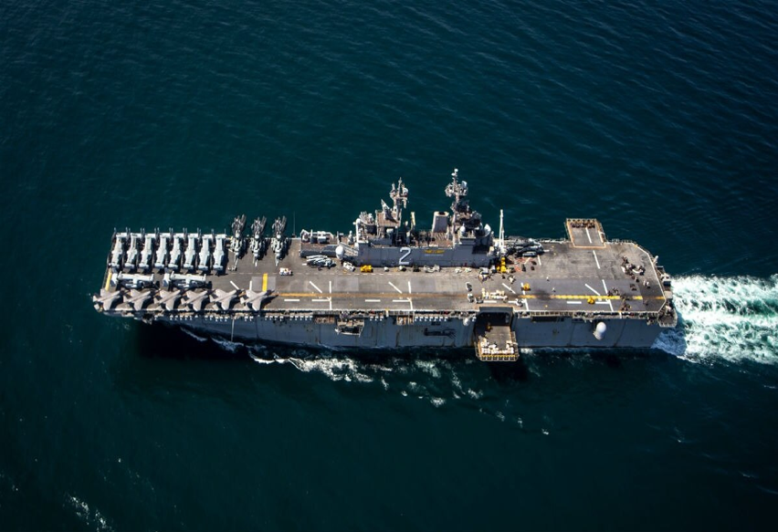 An aerial view of an amphibious assault ship with a landing and launchpad for fighter jets on the ocean.
