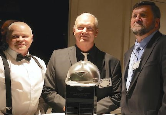 Russellville Plant Manager Gavin Butterworth, Taber President Eric Angermeier, and Gulfport Plant Manager Mike Keenan standing with the NMLP Safety Award trophy during the 2018 holiday party.