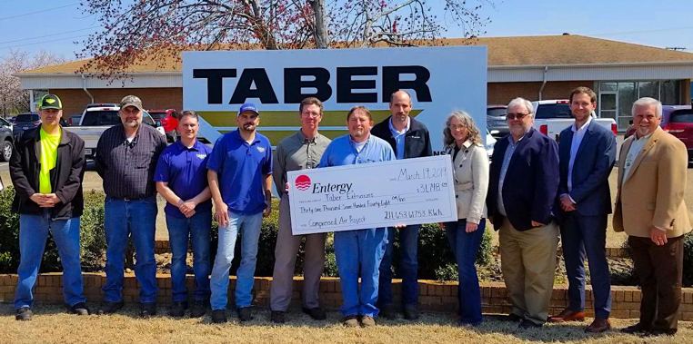 Taber Extrusions employees stand alongside Entergy and CLEAResult personnel in front of the Taber sign at their Russellville location. They are holding an extra-large check for $31,748 – representing Taber's energy savings.