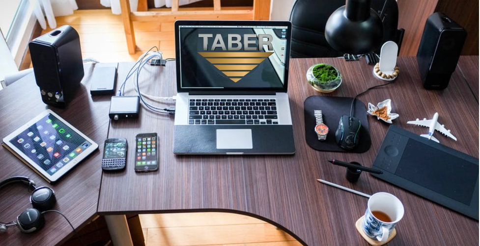 A sleek, modern wooden desk with various consumer electronics neatly organized across the top. Items include a laptop, iPad, two cell phones, small stereo speakers, and headphones.