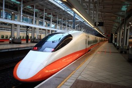 a long, white high speed train with orange trim at the bottom. The train disappears into the distance as it rests at an empty platform with tile floors and a metal roof with a long row of lights and a skylight running down the middle on the roof.