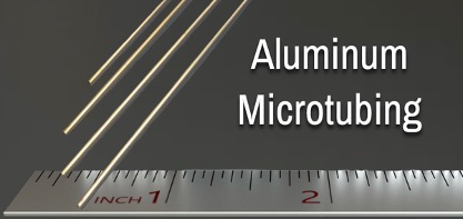 """3D Rendering of a silver ruler measuring approximately 2 inches of space, with 4 tiny aluminum tubes jutting down from the top of the image, barely taking up a few millimeters on the ruler. The words """"Aluminum Mictotubing"""" appear to the right in white."""