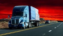 Underneath a fiery red sky, a blue lorry and trailer travel along a paved highway road followed by a car while on the other side of the double yellow line, two empty lanes extend off into the distance.
