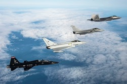 A U.S. Air Force T-38 Talon, British Royal Air Force Eurofighter Typhoon, French Air Force Dessault Rafale, and U.S. Air Force F-22 fly in formation above the clouds on a sunny day.