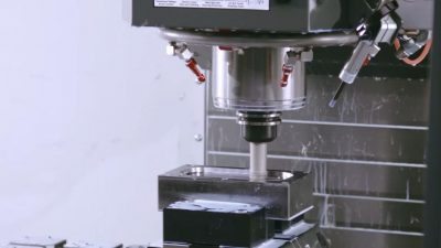 """A close-up of the spindle and nozzles for lubrication and coolant of a CNC machine in full operation working on a metal """"brick."""""""