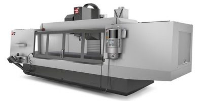 A digital image of a VF-12 CNC machine made by Haas, which is a long rectangular box with four large connected viewing panels to allow operators to see the interior where a vertical column holds a spindle which is used to create aluminum extrusions.