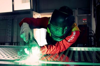 An image of a person wearing a black helmet and a thick red jacket welding a piece of metal, with green light sparking out of the welding machinery.